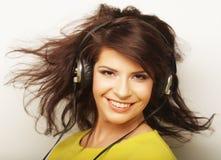 Mujer con música que escucha de los auriculares Baile de la muchacha de la música contra el fondo blanco Fotos de archivo
