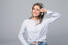Mujer con música que escucha de los auriculares Baile de la muchacha del adolescente de la música contra fondo gris aislado Imagenes de archivo