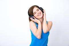 Mujer con música que escucha de los auriculares con los ojos cerrados Fotos de archivo