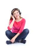 Mujer con música que escucha de los auriculares en jugador Fotos de archivo