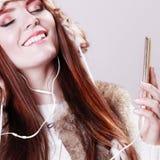 Mujer con música que escucha del teléfono elegante Imagen de archivo libre de regalías