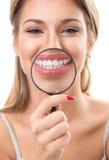 Mujer con magnificar mostrándole los dientes perfectos Imágenes de archivo libres de regalías