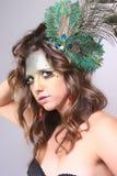 Mujer con maquillaje salvaje con una pluma del pavo real en su pelo Imagenes de archivo