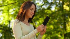 Mujer con mirada del smartphone alrededor, fondo borroso de la naturaleza almacen de metraje de vídeo