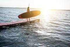 Mujer con paddleboard en el embarcadero al aire libre imagenes de archivo