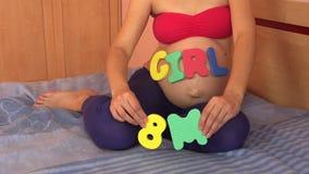 Mujer con palabra de la muchacha en el vientre en 8 octavos meses del embarazo almacen de metraje de vídeo