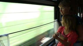 Mujer con paseo de la hija en un tren almacen de metraje de vídeo