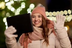 Mujer con PC de la tableta en el árbol de navidad al aire libre Fotos de archivo libres de regalías