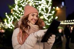 Mujer con PC de la tableta en el árbol de navidad al aire libre Fotografía de archivo