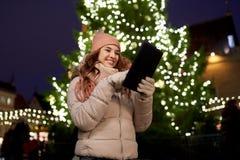 Mujer con PC de la tableta en el árbol de navidad al aire libre Imagenes de archivo