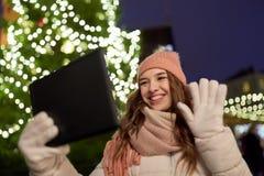 Mujer con PC de la tableta en el árbol de navidad al aire libre Foto de archivo