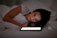 Mujer con PC de la tableta que duerme en cama en la noche Foto de archivo
