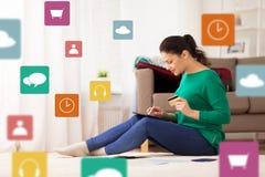 Mujer con PC de la tableta y la tarjeta de crédito en casa Imágenes de archivo libres de regalías