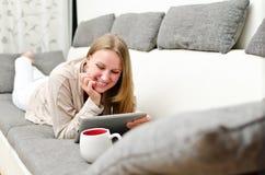 Mujer con PC de la tablilla Imagenes de archivo