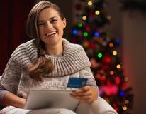 Mujer con PC de la tablilla y de la tarjeta de crédito sonrientes Foto de archivo libre de regalías