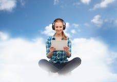 Mujer con PC y los auriculares de la tableta Imágenes de archivo libres de regalías