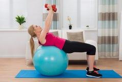 Mujer con pesa de gimnasia mientras que ejercita en bola de la aptitud Foto de archivo