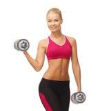 Mujer con pesas de gimnasia de acero pesadas Imagenes de archivo