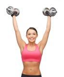 Mujer con pesas de gimnasia de acero pesadas Fotografía de archivo libre de regalías