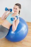 Mujer con pesas de gimnasia en bola del ejercicio en estudio de la aptitud Foto de archivo