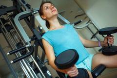 Mujer con pesas de gimnasia en el gimnasio que hace ejercicios Fotografía de archivo libre de regalías