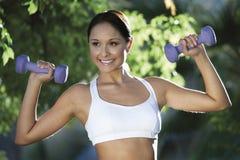 Mujer con pesas de gimnasia en parque Fotografía de archivo