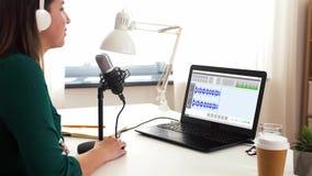 Mujer con podcast de registración del micrófono en el estudio almacen de video
