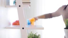 Mujer con polvo de la limpieza del plumero del estante en casa almacen de video