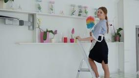 Mujer con polvo de la limpieza del plumero del estante en el hotel metrajes