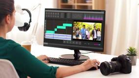 Mujer con programa de editor de v?deo sobre el ordenador port?til en casa almacen de video