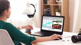 Mujer con programa de editor de v?deo sobre el ordenador port?til en casa almacen de metraje de vídeo