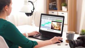 Mujer con programa de editor de v?deo sobre el ordenador port?til en casa metrajes