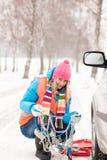 Mujer con ruptura de la nieve del coche de los encadenamientos de neumático imágenes de archivo libres de regalías