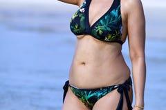 Mujer con símbolo de la forma de la demostración del bikini en la playa Foto de archivo