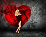 Mujer con salpicar el corazón en fondo oscuro foto de archivo