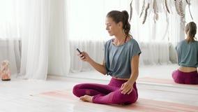Mujer con smartphone en el estudio de la yoga almacen de video