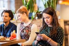 Mujer con smartphone y amigos en el restaurante Imagen de archivo libre de regalías