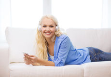 Mujer con smartphone y los auriculares en casa Imágenes de archivo libres de regalías