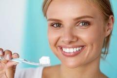 Mujer con sonrisa hermosa, dientes blancos sanos con el cepillo de dientes imágenes de archivo libres de regalías