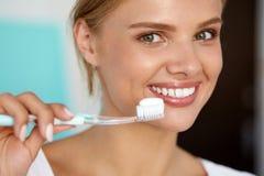 Mujer con sonrisa hermosa, dientes blancos sanos con el cepillo de dientes Imagen de archivo libre de regalías