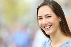 Mujer con sonrisa perfecta y los dientes blancos que le miran Foto de archivo