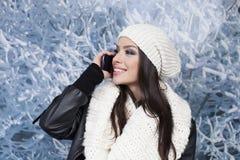 Mujer con sonrisa usando un teléfono elegante Fotos de archivo libres de regalías