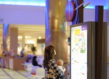 Mujer con su bebé en una alameda de compras Foto de archivo