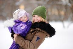 Mujer con su hija del niño en el parque del invierno Imagenes de archivo
