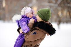 Mujer con su hija del niño en el parque del invierno Imagen de archivo
