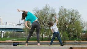 Mujer con su hijo que hace yoga por la charca, al aire libre almacen de video