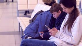 Mujer con su hijo que hojea en los teléfonos móviles en el vuelo que espera del pasillo del aeropuerto para, vista lateral almacen de metraje de vídeo