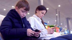 Mujer con su hijo que juega a juegos en los teléfonos móviles en vuelo que espera del pasillo del aeropuerto para almacen de metraje de vídeo