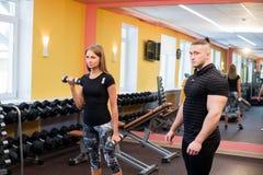 Mujer con su instructor personal de la aptitud en el gimnasio que ejercita la gimnasia del poder con un barbell fotos de archivo