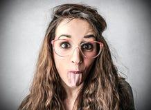 Mujer con su lengua pegada hacia fuera Imagenes de archivo